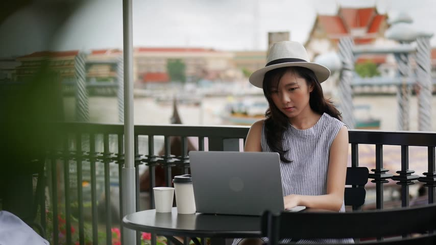 Young asian woman using laptop working at cafe in thailand. Businesswoman drinking a coffee cup outdoors at coffee shop. Стоковые видеозаписи