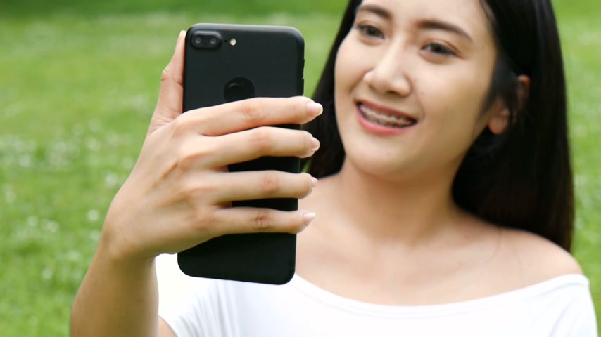 Beautiful asian young woman taking photo selfie using smart phone at public park. Стоковые видеозаписи