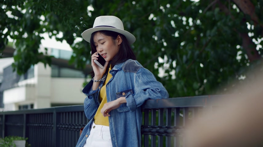 Young beautiful asian woman smiling, happy, talking on the phone. Стоковые видеозаписи