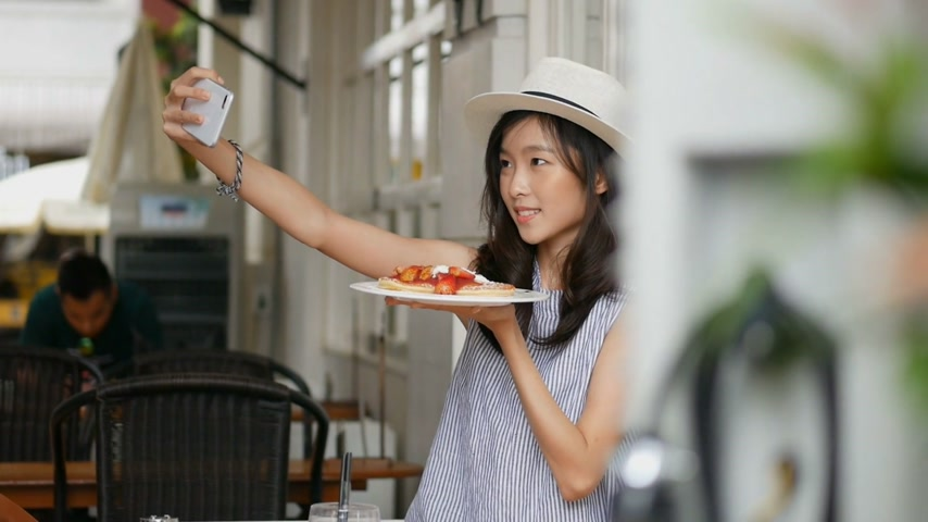 ciasta : Beautiful asian woman taking selfies on a smartphone. Young asian girl take photo with pancake at cafe shop.