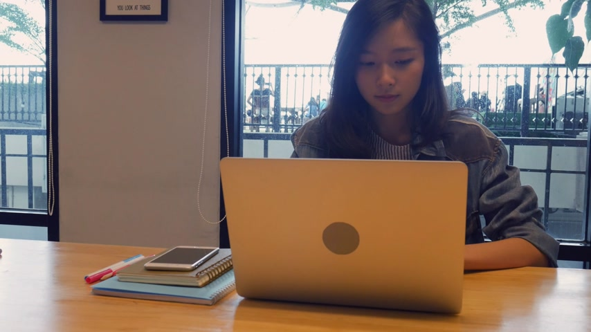 Businesswoman using laptop at office. Beautiful asian female shopping online in office.  Talking on phone inside meeting room.