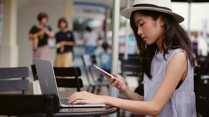 Young asian woman using laptop working at cafe in thailand. Businesswoman talking on phone at coffee shop