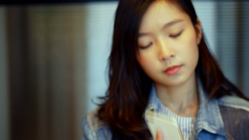 Businesswoman talking on phone inside meeting room at office.