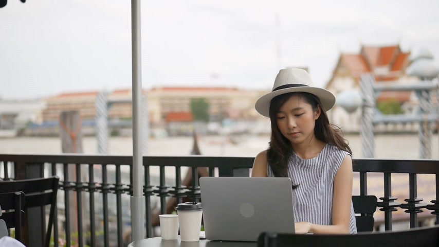 Young asian woman using laptop working at cafe shop. Beautiful girl sitting working at coffee shop.