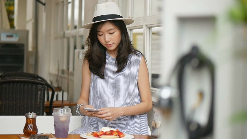 Young asian woman take a photo pancake at cafe. Technology and social networks concept.