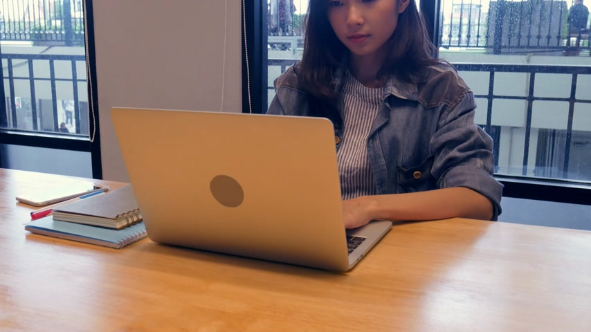 Businesswoman using laptop inside meeting room at her office.
