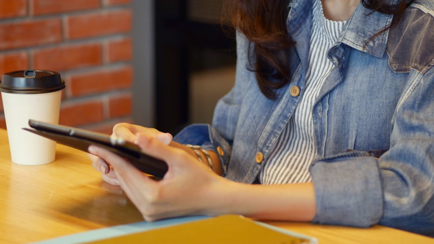 Young caucasian woman using digital tablet for her business. Woman sitting at coffee shop.