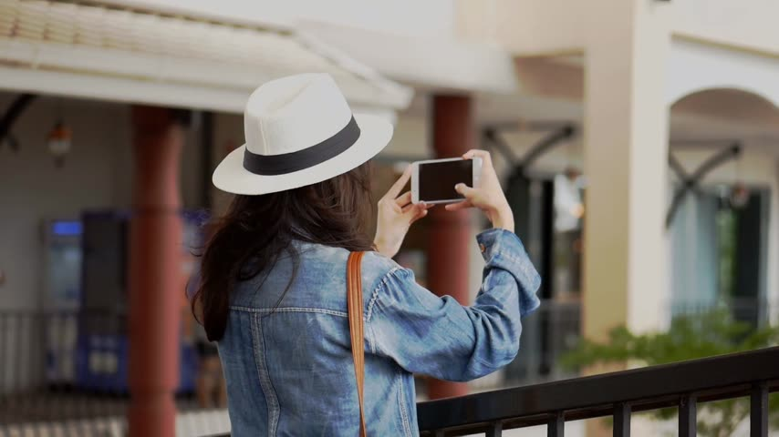 Young asian woman using smartphone take photo around community mall. Beautiful asian girl tourist travel to thailand.