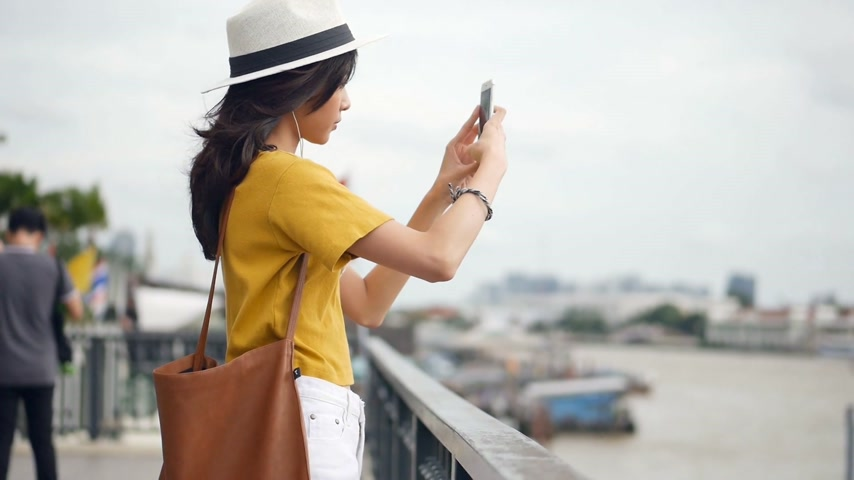 Young asian woman using smartphone take photo around chao phraya river. Beautiful asian girl tourist travel to thailand. Стоковые видеозаписи