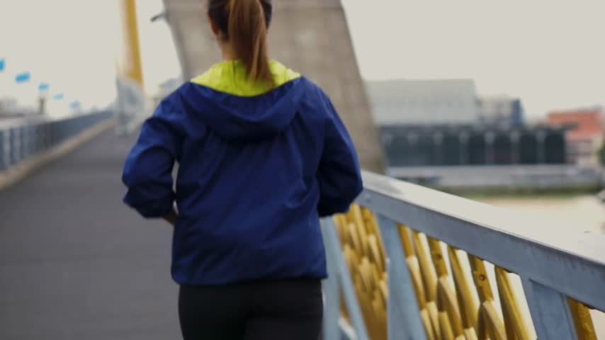 Slow Motion - Young asian woman running on the bridge before sunset in bangkok thailand. Female jogger training outdoors concepts.