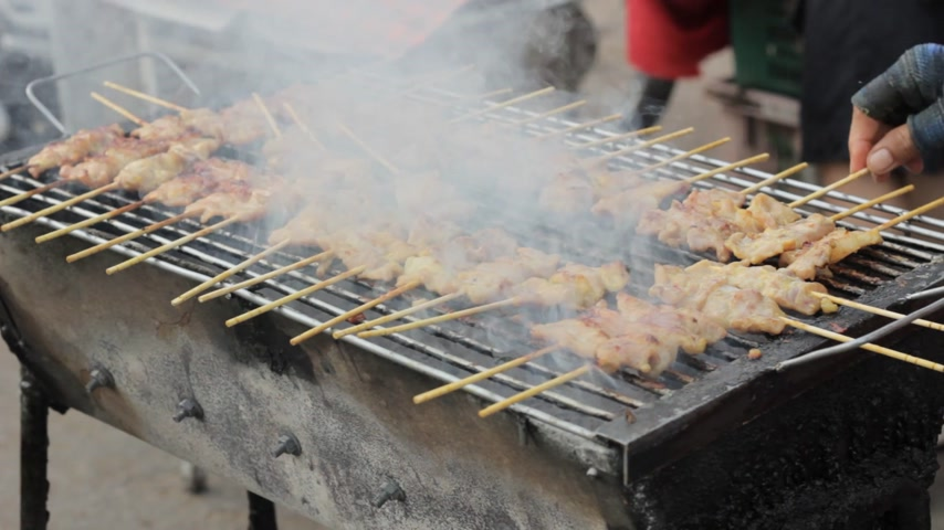 nekvalitní potraviny : woman cooking delicious pork sticks on an open grill on in thai market