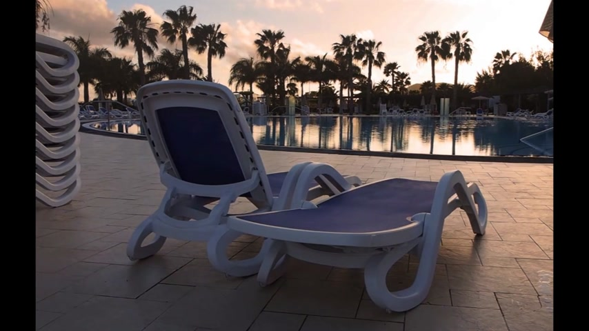 View of the two plastic reclaining seats by the swimming pool in the resort in Playa Blanca, Lanzarote , Spain