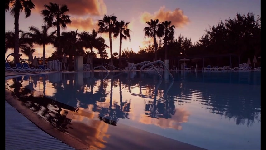 spanyolország : Sunset over the swimming pool in the resort in Playa Blanca, Lanzarote, Spain Stock mozgókép