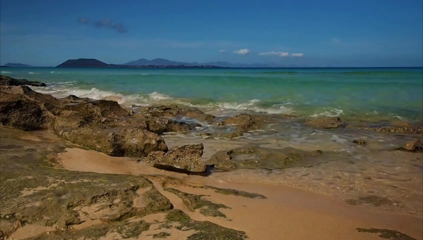 Beautiful turquoise blue sea in Corralejo Dunes National Park in Fuerteventura, Canary Island, Spain with Los Lobos Island in the background