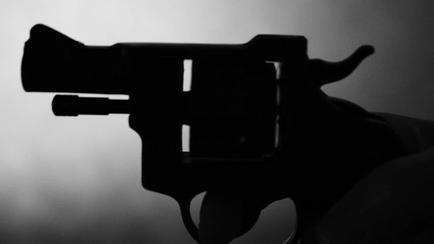 disarming : Silhouette of a mans hand with a handgun,real time Stock Footage