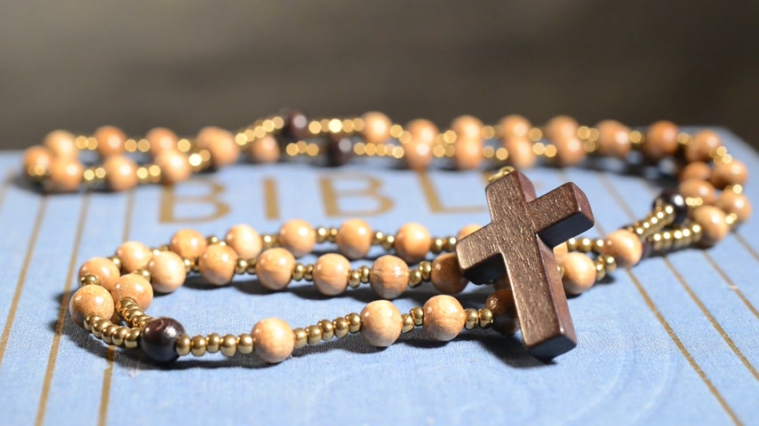 modlitba : Rotation of wooden rosary on the Bible. real time, no sound,