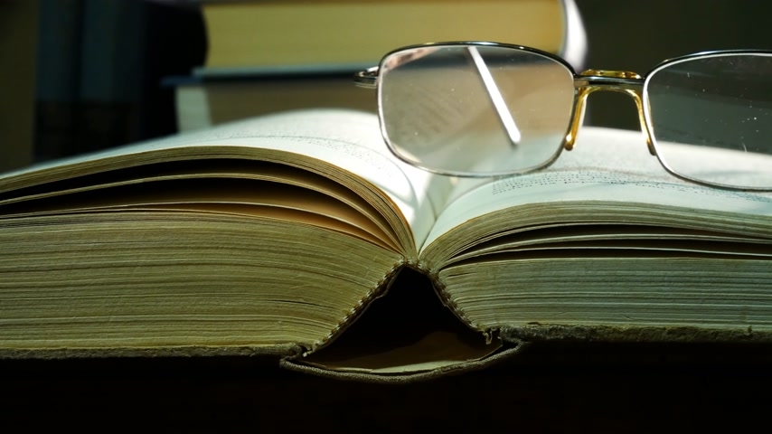 ansiklopedi : Open Book with Glasses on the Used Table. Sliding.