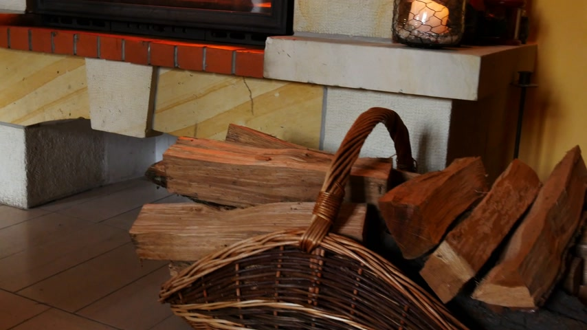 Basket with firewood in front of fireplace. Panning. Stok Video