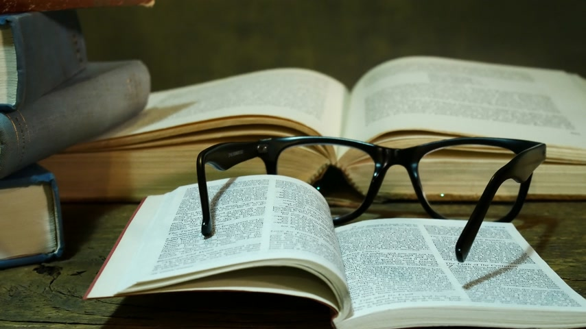 Open Bible with Glasses on the Used Table. Zoom in. Stok Video