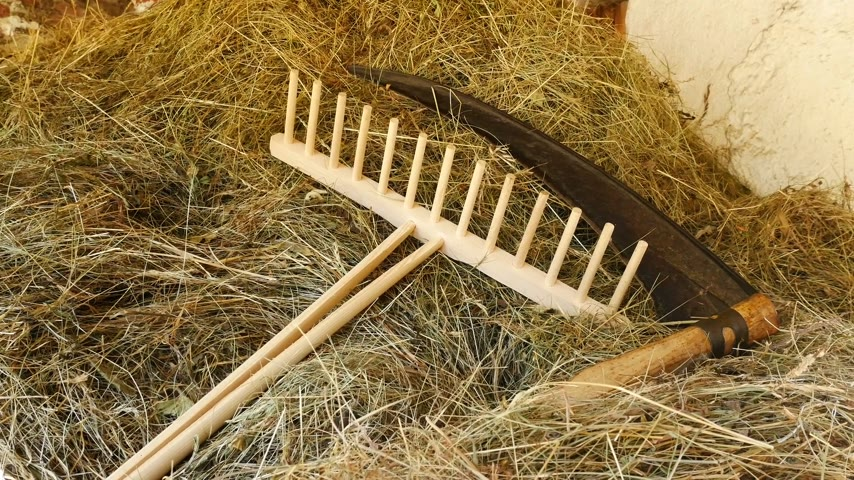 A scythe and a rake with hay. Zoom in.