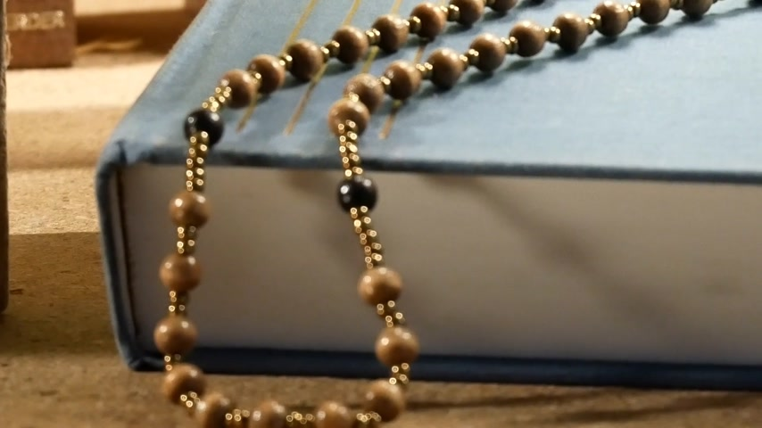 slider shot : Wooden Rosary on the Bible. Panning