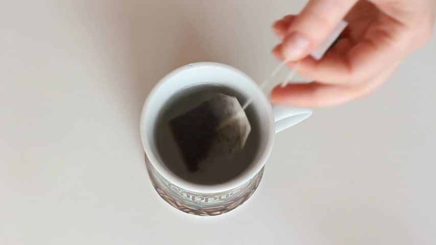 tea bag : A cup of brewed black tea in a bag.  Stock Footage