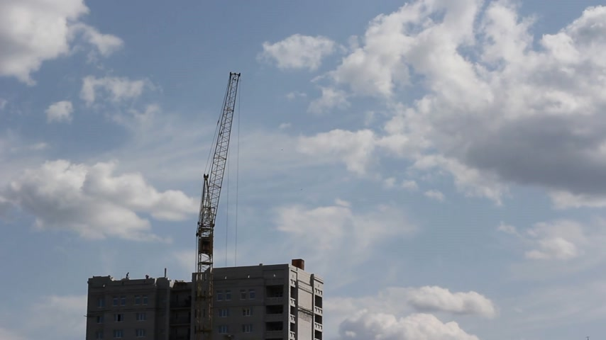 time machine : Tower cranes against blue sky, with clouds. Timelapse.
