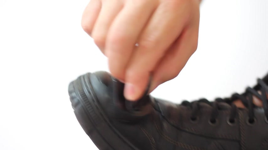 brilhar : Man polishing leather black shoes on white background Stock Footage