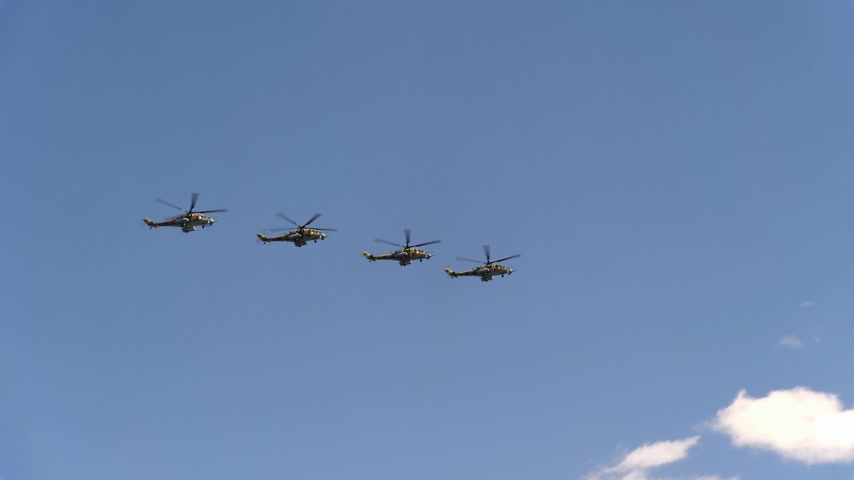mi : Combat helicopters Mi-24 fly in blue sky Stock Footage