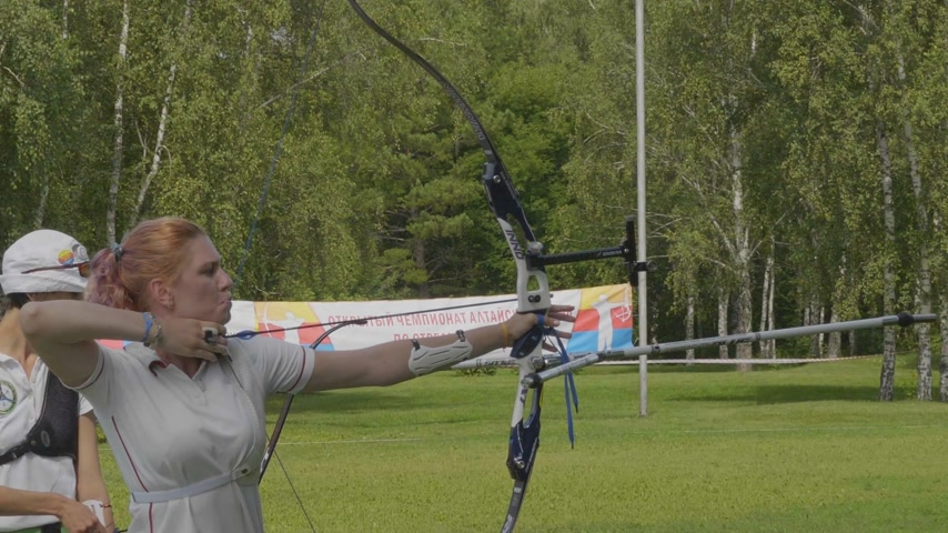 strzelec : BARNAUL - AUGUST 6: Attractive female archer bending a bow and aiming in the target on August 6, 2017 in Barnaul, Russia.