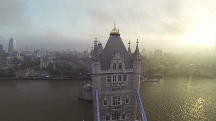 london england : Camera flying above London Bridge over Thames river. At sunset. Stock Footage