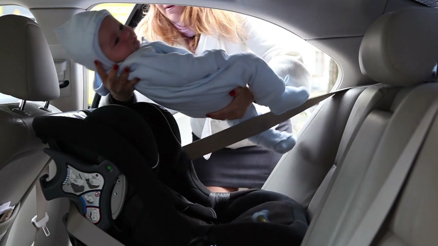 anne : mother put child in safety car seat Stok Video