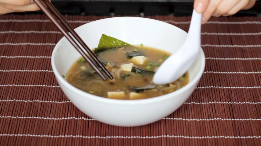 kombu : Female hands stir miso soup in white bowl and pick out ingredients with chopsticks. Misoshiru is traditional japanese food often eaten for breakfast.