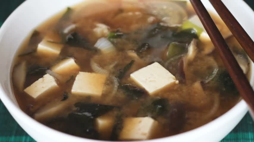 kombu : Extreme close up of sprinkling big bowl of miso soup with diced green onions. Miso soup is japanese food traditionally eaten with chopsticks. Main ingredients are miso paste, tofu, wakame seaweed.