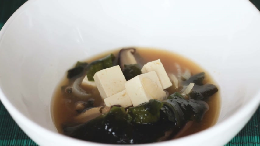 kombu : Close up of japanese miso soup poured into white bowl. It is traditional japanese food usually made of tofu, shiitake mushrooms, wakame seaweed and miso paste and is often eaten for breakfast. Stock Footage