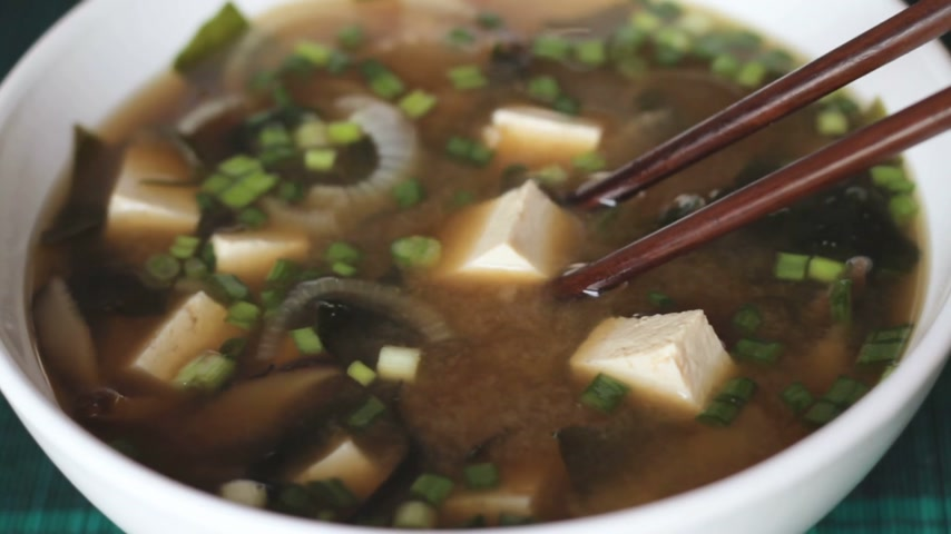 kombu : Close up of picking up a dice of tofu with chopsticks from big white bowl of miso soup. It is traditional japanese food. Main ingredients are miso paste, tofu, wakame seaweed and shiitake mushrooms. Stock Footage