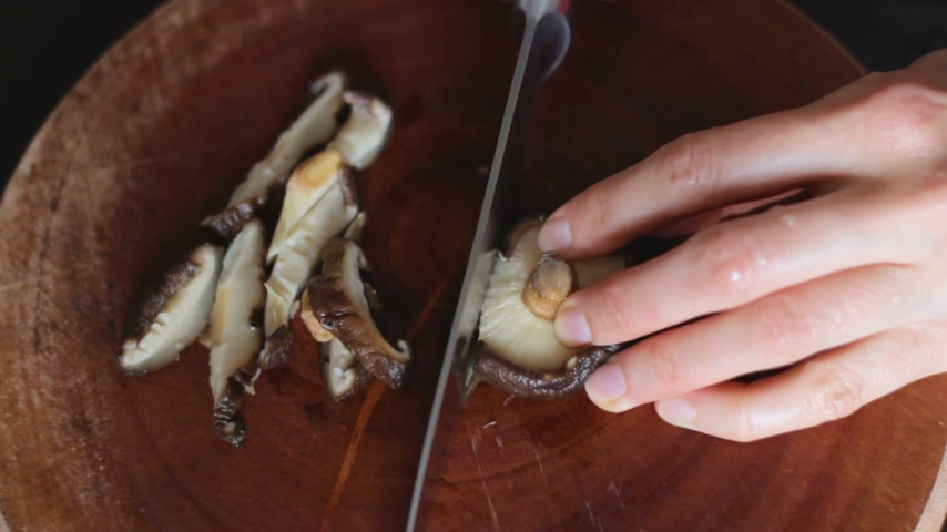 shiitake : Close up of female hands cutting previously soaked shiitake mushrooms on round wooden board. Shiitake is a famous ingredient for miso soup (japanese traditional dish). Table top view. Stock Footage