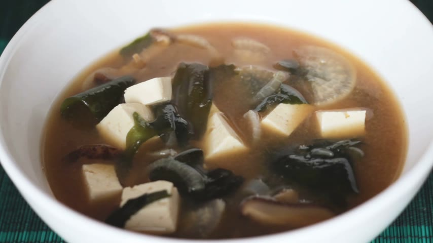 kombu : Close up of pouring miso soup with a scoop into white bowl. It is nourishing traditional japanese food. Main ingredients are miso paste, tofu, wakame seaweed and shiitake mushrooms. Table top view.