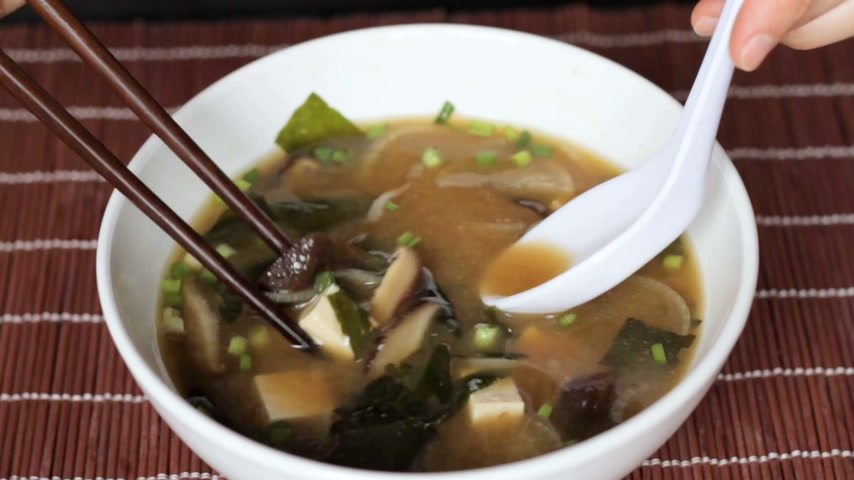 kombu : Female hands take out various ingredients from miso soup with chopsticks and white spoon. Close up. Misoshiru is traditional japanese food usually eaten with chopsticks. Stock Footage