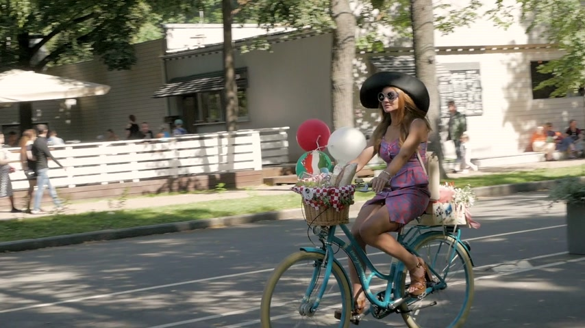 participante : MOSCOW - AUGUST 6, 2017: Beautiful elegant woman in retro clothes riding bicycle on annual female bicycle parade Lady on Bike in Sokolniki park