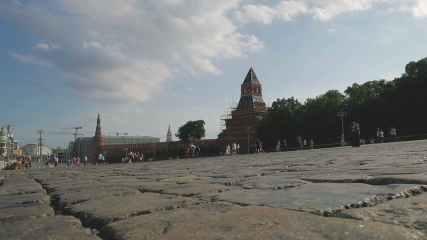 vasilevsky : Panning shot of unidentified people walking along Vasilevsky descent near the Kremlin walls and Red Square in Moscow, Russia. Low angle view.