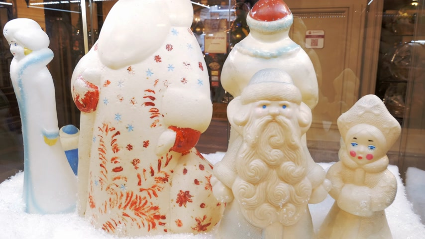 ded : Soviet vintage santa claus (ded moroz) and snegurochka figurines made of plastic on display in shopping mall. Panning, close up. 4K