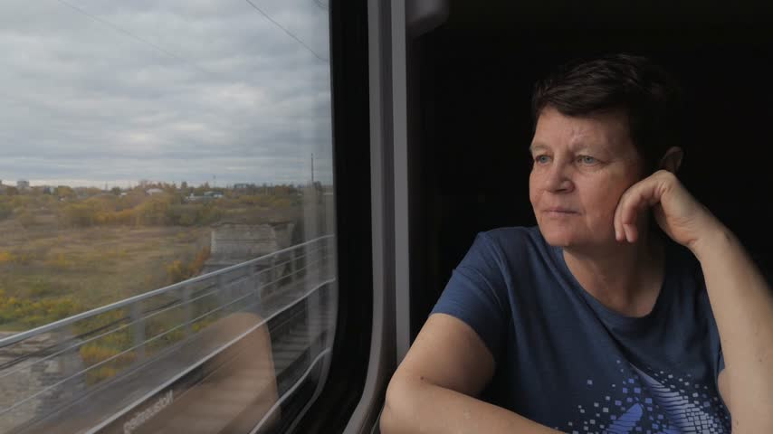 меланхолия : Attractive smiling elderly woman in pensive mood sitting near window in train moving on bridge. Стоковые видеозаписи