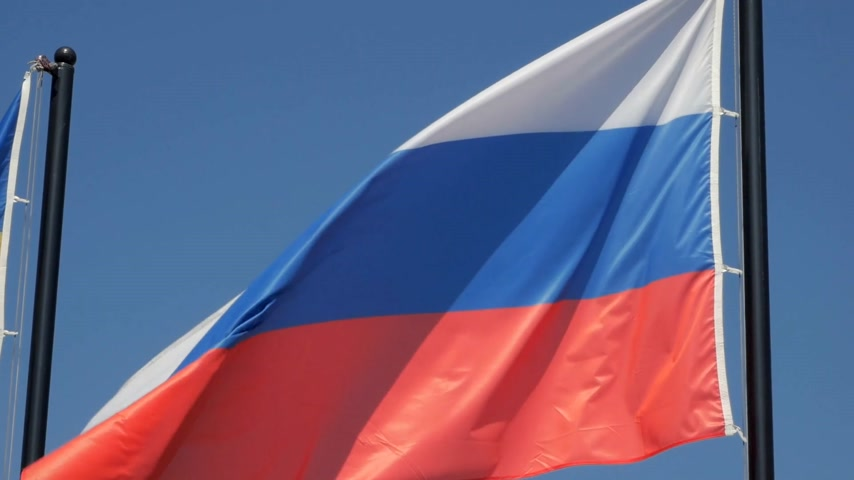 Close up of flying flag of Russian Federation against blue sky