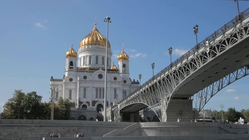 Boat moving under Patriarshy bridge, along Moskva river embankment with Christ the Saviour Cathedral with golden domes