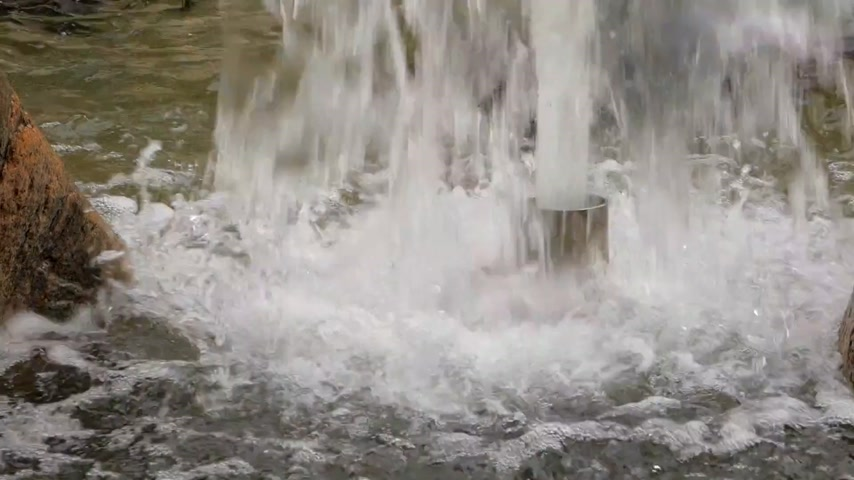 Stream of water spurting from pipe in fountain