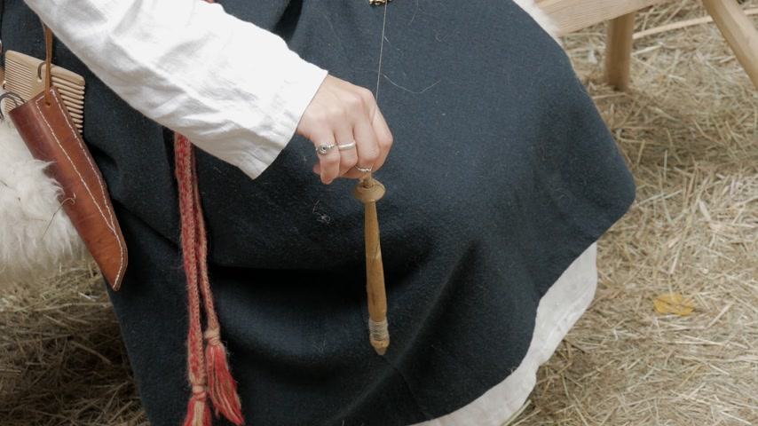 Reconstruction of medieval hand spinning. Woman spinning fiber into single strand of yarn with drop spindle