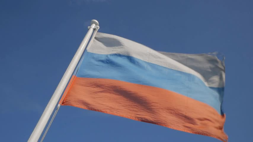 Flying banner of Russian Federation against blue sky Stock Footage