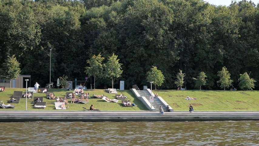 солнечные ванны : Beautiful Moskva river embankment on Sparrow Hills with lush green trees, summer beach and people lying on loungers and enjoying hot summer in Moscow, Russia