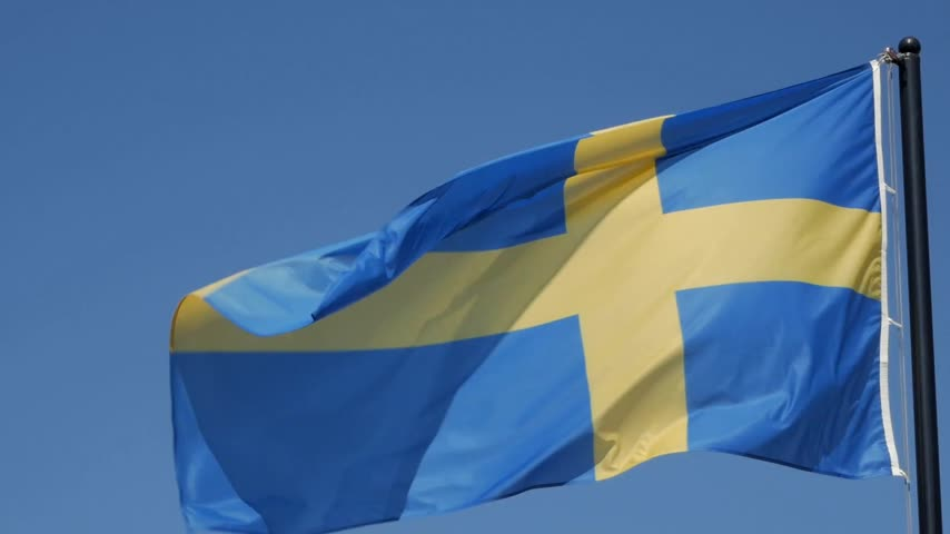Close up of flying banner of Sweden against blue sky Stock Footage